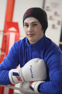 Leaning on boxing ring ropes with smile after training in the gym.